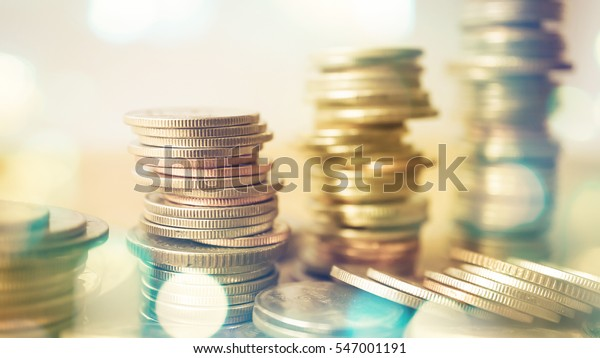 rows of coins and blurred bokeh for finance and banking concept