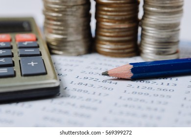rows of coins for finance and banking with chart and pencil and calculator concept