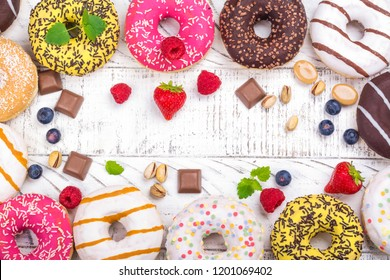 Rows of colorful donuts with sprinkles and different fillings on white background. Copy space