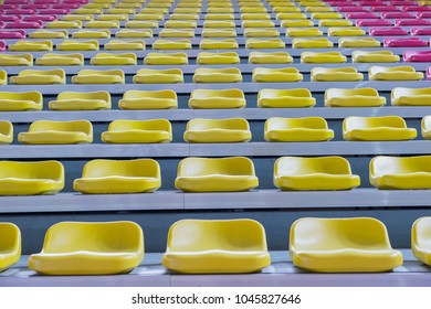 Rows of colorful empty seat in football indoor stadium
