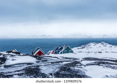 Rows of colorful inuit houses hiding in the rocks with fjord in the background, suburb of arctic capital Nuuk, Greenland