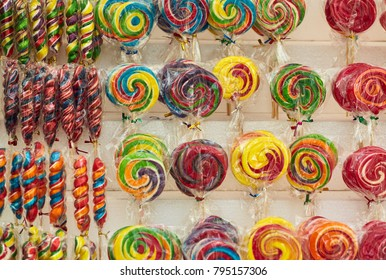 Rows of colorful spiral and rainbow-swirl lollipops on display on the shelves in the market,