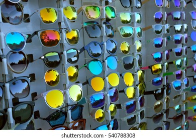 Rows of colorful sunglasses with mirrored lenses in a store display