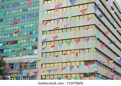 Rows of colorful traditional bunting in front of modern office building facades in downtown Chihuahua, Mexico, for Mexican Independence Day, September 16