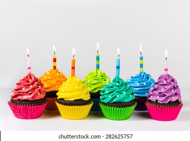 Rows of colourful cup cakes decorated with birthday candles and sprinkles.