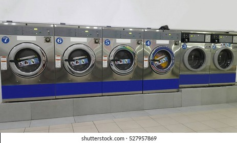 Rows of commercial industrial washing machines at laundromat/ laundrette for public / consumer's use