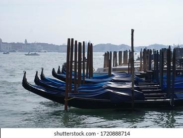 Rows of covered gondolas in lagune of Venice