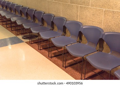 Rows of dark grey  chairs in the waiting area. Empty chairs lined-up