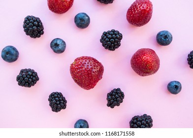 Rows of delicious freshly picked bluberry, blackberry and strawberry on pastel colored pink background.