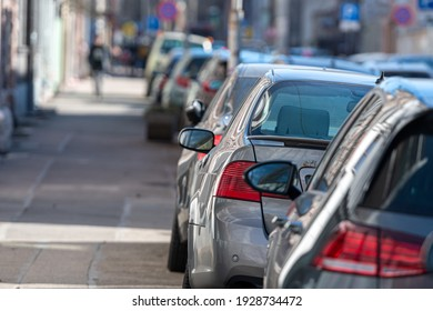 rows of different cars parked along the roadside in crowded city, close-up, selective focus