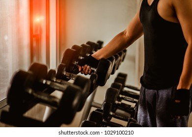 Rows of dumbbells in the gym with hign contrast and monochrome color tone.