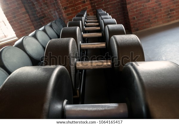 Rows of dumbbells in the gym with hign contrast and reflection in mirror