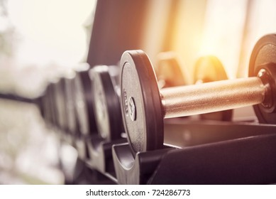 Rows of dumbbells in the gym with sunset.