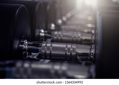 Rows of dumbbells in the gym.background of black dumbbells on rack for training equipment in fitness