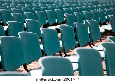 Rows of empty blue chairs for audience