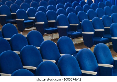 The rows of empty blue seats in the movie theater or conference hall