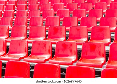 Rows empty bright red plastic seats in a stadium