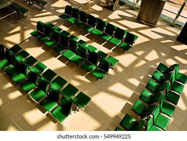 Rows of empty chairs or benches at airport with evening sunlight shade at dawn given feeling of lonely or waiting for someone.