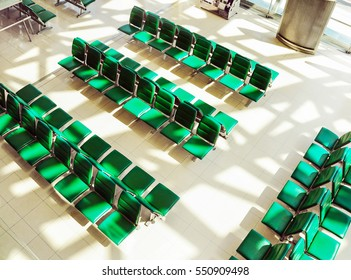 Rows of empty chairs or benches at airport clean waiting area with bright morning sunlight making shadow of building structure. Shot from top view.
