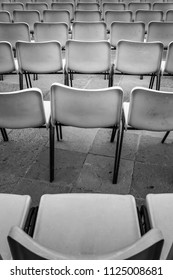 Rows of empty chairs representing the solitude or  failure concept. Collective loneliness.