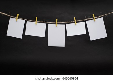 Rows of empty photo frames hanging with clothespins on dark background