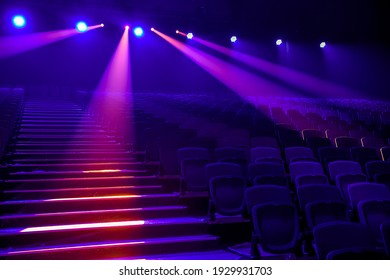 Rows of empty seats in the concert hall in the colored spotlights.