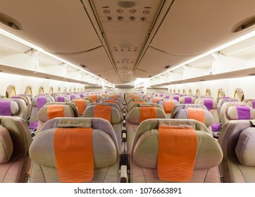 Rows of empty seats on a modern wide body jet aircraft, overhead bins open and waiting for luggage when passengers board the economy section of the aircraft.