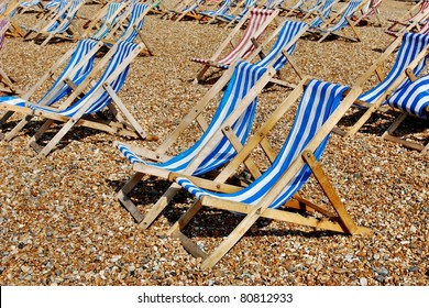 Rows of empty traditional striped deckchairs on Brighton beach, England, UK