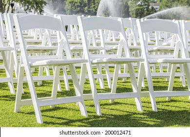 Rows of empty white folding chairs sitting on a lawn.