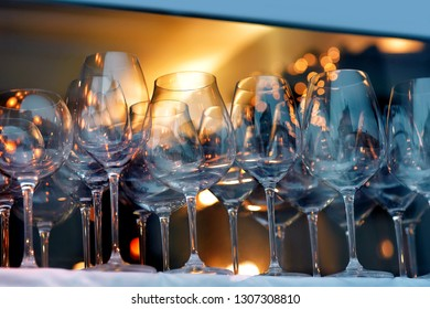 Rows of empty wine, brandy, cocktail glasses with lighting showcase background in pub or night bar. Wine glasses in row on the shelf behind the window with colorful light. Beverage party concept