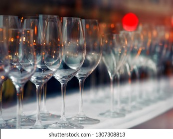 Rows of empty wine glasses with lighting showcase background in pub or night bar. Wine glasses in row on the shelf behind the window with colorful light. Interior decoration and beverage party concept
