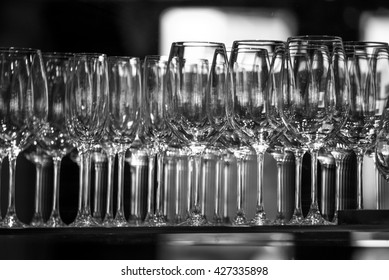 Rows of empty wine glasses on the showcase, black and white photography. Lots of wine glasses, Wine glasses lined, Wine glasses in row on bar  on light grey background