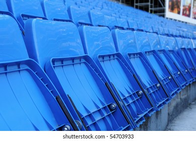 Rows of folded plastic blue seats at an empty soccer football sports stadium.