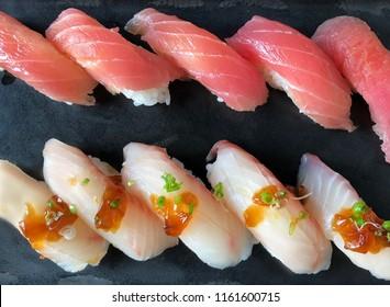 Rows of fresh Japanese Akami Nigiri Sushi (Makuro) and  Hamachi Yellowtail Nigiri Sushi on black dish serving on black ceramic plate