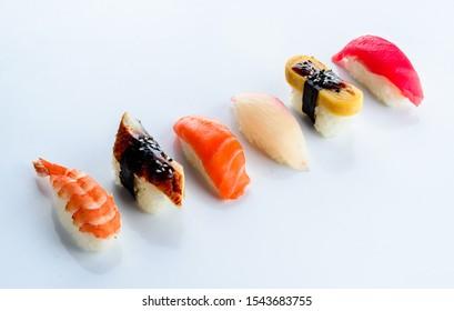 Rows of fresh Japanese Akami Nigiri Sushi (Makuro) and Hamachi Yellowtail Nigiri Sushi. Set of nigiri on a light background