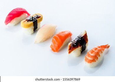 Rows of fresh Japanese Akami Nigiri Sushi Makuro and Hamachi Yellowtail Nigiri Sushi. Set on a light background