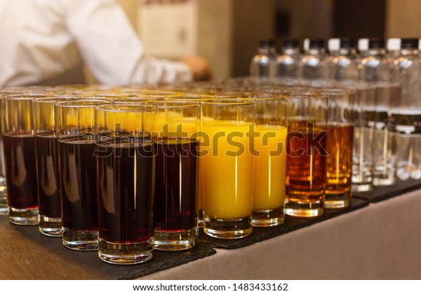 Rows of glasses with non alcoholic drinks, orange juice and water. Drinks on a buffet table. Catering