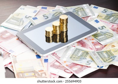 rows of gold stack coins, tablet and euros