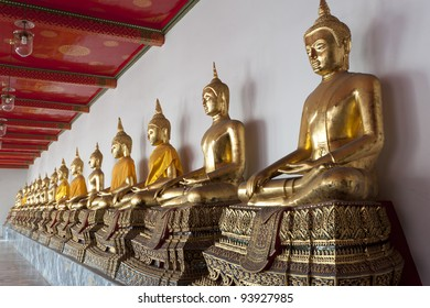Rows of golden Buddha figures in a Bangkok Temple Thailand