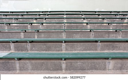 Rows of green wood and concrete bleachers.