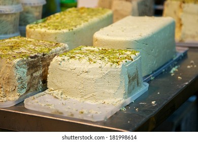 rows of halvah on market stand in Israel. Pieces of halva with nuts on a cutting board