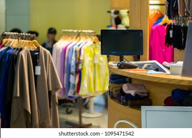 Rows of hangers with man and woman outfit and cash desk terminal in small store