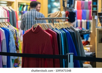 Rows of hangers with man and woman outfit in small store
