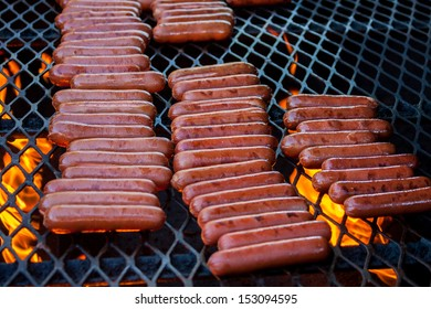 Rows of Hot Dogs cooking on a large grill