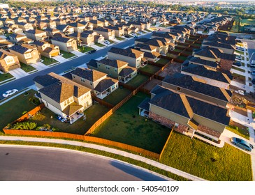 Rows and Rows Of Houses Austin Suburb Community Aerial Shot over New Home Development with golden triangle rooftops and perfect square yards. A Modern Layout with Houses very close together