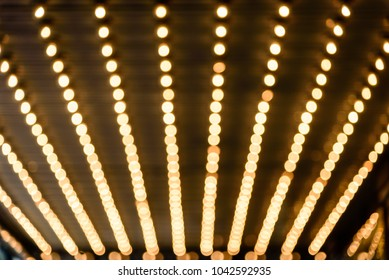 Rows of illuminated globes under the marquee as often used at entrance to theatres and casinos