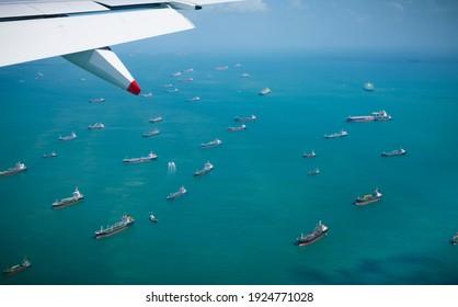 Des rangées de navires à cargaison industriels font la queue sur l'océan à l'extérieur de Singapour. Le fret maritime international se profile à l'horizon. Vue aérienne de la mondialisation des transports.