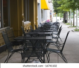 Rows of iron tables on a sidewalk outside a restaurant