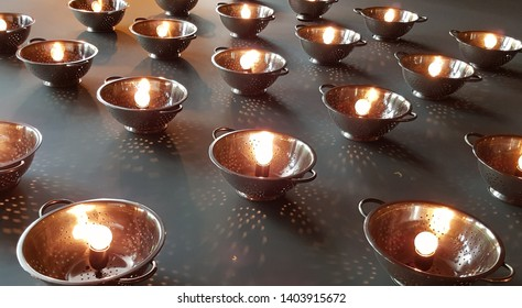 Rows of lamps made from colanders with glowing glass bulbs inside. Abstract background. Light dots from a bulb light on matte grey background. Metal colander chandeliers closeup. Geometric bowl shapes