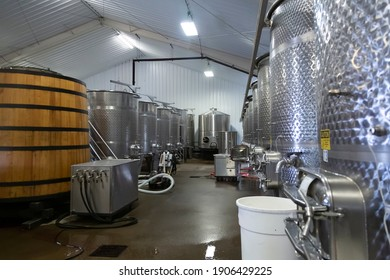 Rows of Large Stainless Steel Commercial Wine Holding Fermentation Blending Tanks and Wooden Casks, Cement Ground, Indoors - Oregon